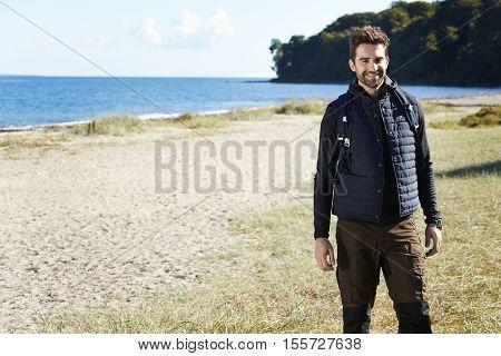 Happy hiker at beach smiling at camera