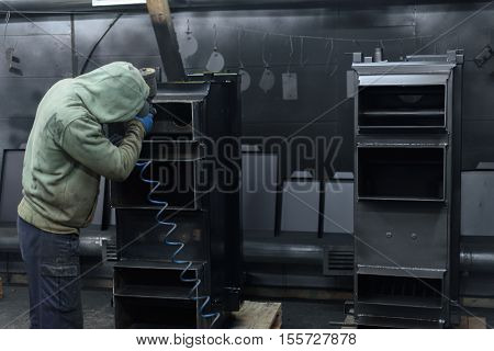 Man in working suit paints solid fuel boiler on the plant