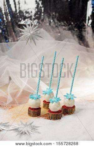 Lollypops side view on the snow. Decorated with sugar snowflakes. Vertical frame.