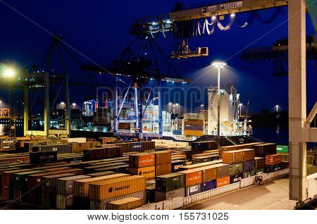 Hamburg, Germany - May 10, 2011: The Buchardkai Container Terminal in Hamburg at night full of containers waiting for their passage on a container ship like the one in the background