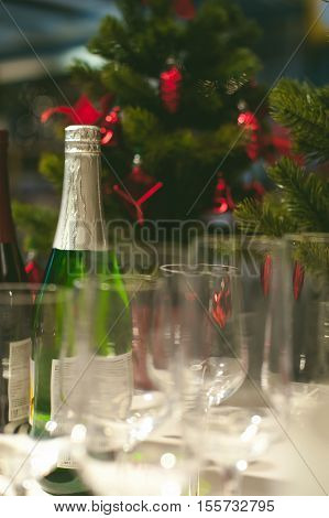 Bottle Of Champagne And Wine Glasses On The Background Of The Christmas Tree, Blurred Bokeh. The Atm