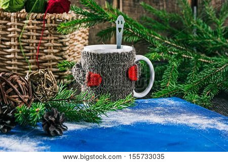 Mug with woolen warmer on the table with yarn balls and christmas decorations