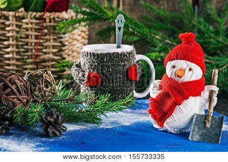 Handmade yarn snowman holding shovel on the background of christmas decorations and mug of hot drink