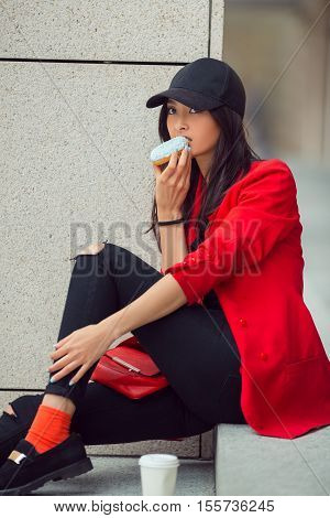 Asian beautiful woman eating a donut with coffee sitting on steps on street, fast food concept outdoors. Busy businessman have no time.