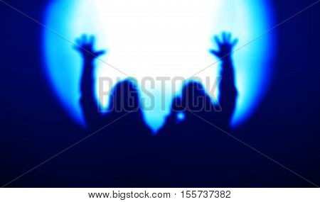 Blue couple silhouettes with hands up in light of floodlight backdrop hd