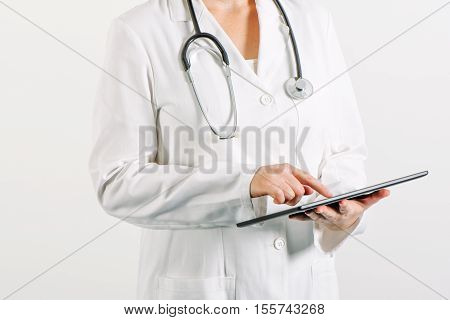 Female general medical practitioner using tablet computer in hospital office