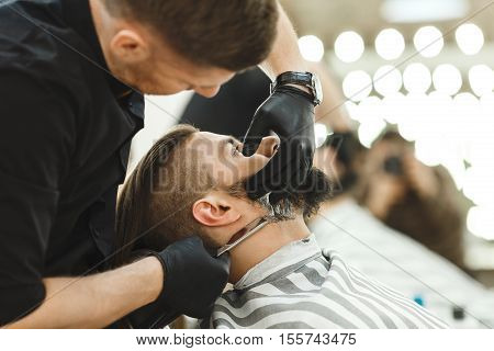 Barber wearing black shirt and gloves making a beard form with razor for man with dark hair and beard at barber shop, copy space, portrait.