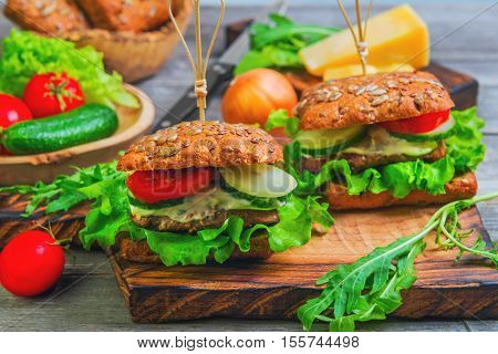 Two sandwich burger with meat and vegetables. Ingredients for cooking sandwiches burgers and fresh vegetables cucumbers tomatoes onions lettuce. Mayonnaise sandwich sauce. Gray wooden background.