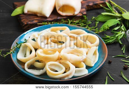 Boiled calamari squid rings on blue ceramic plate cooked squid on cutting rings on board. Herbs for calamari squid rings thyme sage rosemary black wooden background.