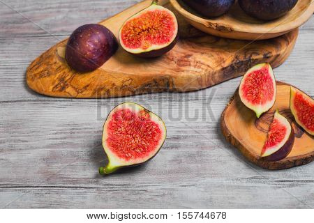 Violet Blue figs whole fruit figs cut into pieces on a board of wood of olive light white wooden background