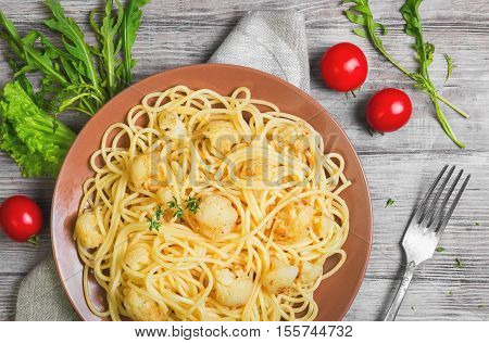 Italian pasta spaghetti on brown plate with cauliflower. Green Spaghetti with Cauliflower thyme lettuce cherry tomatoes cloth. Light white wooden background. Top view