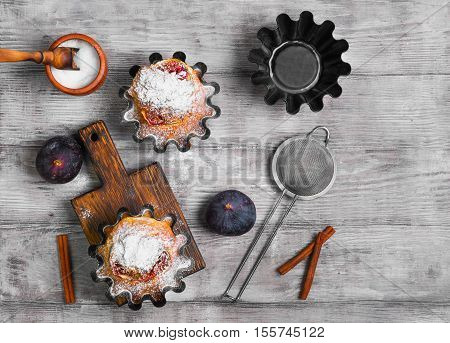 Baked Muffins cake with figs sugar powder. Fresh fruit muffin figs. Metal molds for muffins cinnamon board. Light white wooden background. Top view