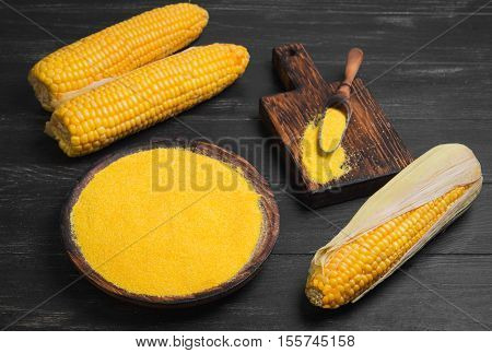 Fresh Corn and corn grits polenta in wooden bowl on wooden black table background. Corn grits polenta in wooden spoon. Not cooked corn polenta.
