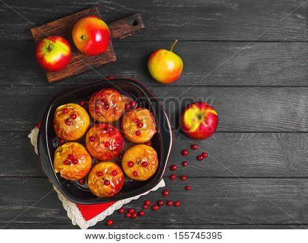 Baked apples baking in oven. Fresh apples for baking on board. Sauce for baked apples red berries. Dark black wood background. Garden apples. Top view blank space.