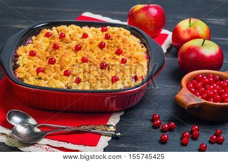 Dessert pie crumble cake apples red berries cranberries. Fresh apples berries for pie crumble cake cloth. Red Black ceramic baking pan cake crumble. Wooden dark background.