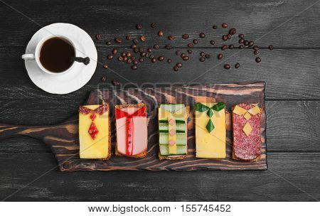 Breakfast for men. Figured sandwiches coffee. Sausage sandwiches cheese vegetables. Concept Breakfast for the day men father's day business lunch. Dark black wood background. Top view.