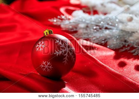 A Red christmas ball on red satin