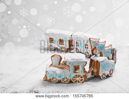 Gingerbread Cookies in the form of train. Christmas cookies train covered with white icing. Christmas Holidays sweets Gingerbread Cookies train. New Year card with snow Christmas gingerbread cookies train white blue.