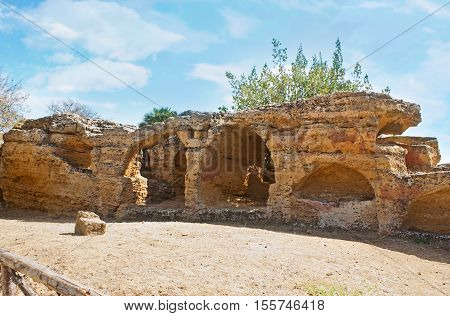 The massive rock with carved arches for the tombs known as Arcosolia Agrigento Sicily Italy.