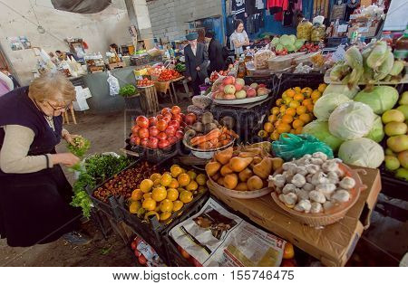 SIGNAGI, GEORGIA - OCT 7, 2016: Woman making choice on vegetable market with fresh tomato salat and other farmer's products on October 7, 2016. Signagi of Kakhetia has a population 2.200