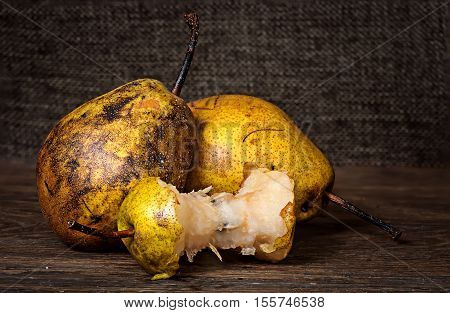 Two pears and stub on wooden table background sacking