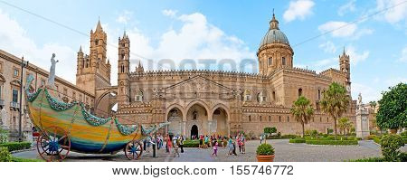 PALERMO ITALY - OCTOBER 2 2012: Avenue of Vittorio Emanuele decorated with the colorful carriage of Santa Rosalia dedicated to her feast with the carved stone Cathedral on background on October 2 in Palermo.