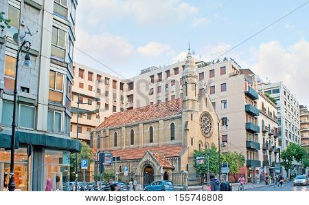 PALERMO ITALY - OCTOBER 2 2012: The small Holy Cross Anglican Church is sendwiched among the modrern buildings of crowded Roma Street with its stores and malls on October 2 in Palermo.