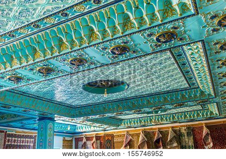 KAIROUAN TUNISIA - AUGUST 30 2015: The ceiling of the rug store decorated with fretwork and colorful Islamic patterns on August 30 in Kairouan.