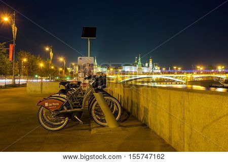 MOSCOW RUSSIA - MAY 10 2015: The municipal bicycles on Prechistenskaya embankment of Moskva River with the Greater Stone Bridge and Kremlin on the background on May 10 in Moscow.
