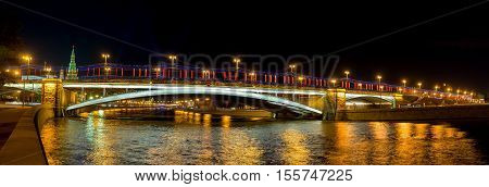 The view from Prechistenskaya embankment of moskva River on the Greater Stone Bridge in bright evening lights reflecting in dark water Moscow Russia.