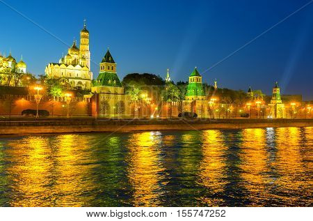 The lights of Kremlin's embankment gives the Moskva river golden reflection Moscow Russia.