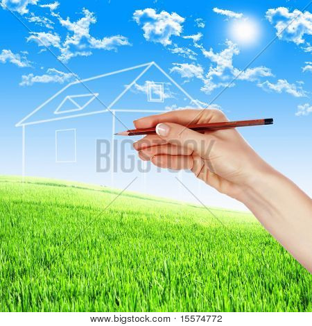 Female hand with a pencil draws a house of clouds against the sky