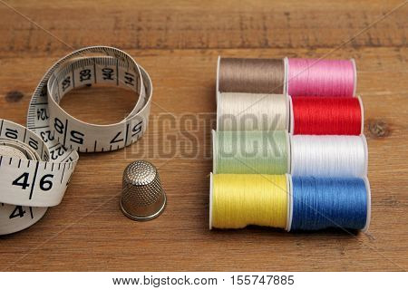 Multi-colored Cotton Reels, Tape Measure And Thimble On A Wooden Sewing Table