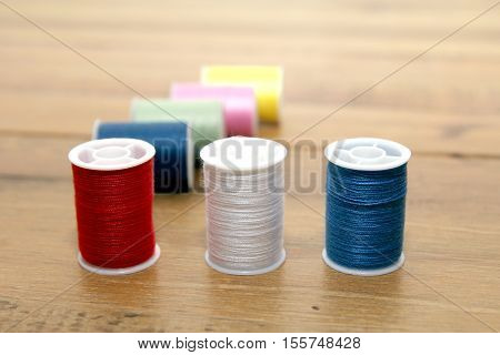 Multi-colored Cotton Reels Or Bobbins On A Wooden Needlework Table