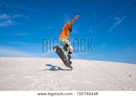 Snowboarder wearing a scarf to protect against sand is jumping on a sand dune. Sand boarding in desert. Low point shooting. Wide angle.