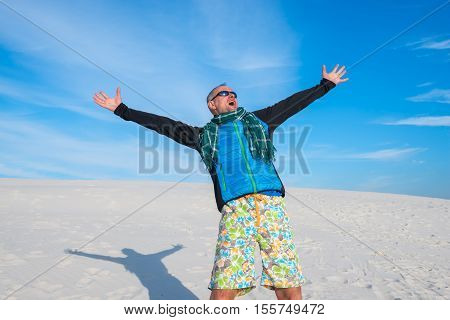 Happy man with arms outstretched by the desert on the background of the bright blue sky. Concept - happiness and success. Wide angle.