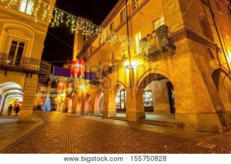 Evening street in old town of Alba, Italy decorated and illuminated for Christmas holidays.