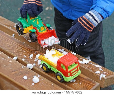 Part of the image of a small child who is standing near a wooden bench covered with snow. The child clears snow from a bench using a toy excavator.