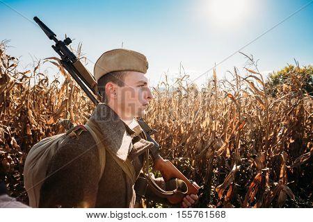 Teryuha, Belarus - October 3, 2015: Unidentified re-enactor dressed as Soviet russian soldier goes along field road.