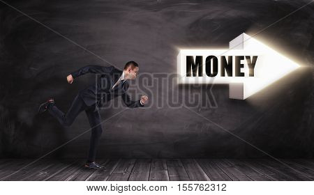 Businessman in profile running in the direction of the big white arrow with the title 'MONEY', pointing right all on the background of the black wall. Business and management. Way to success. Earning money.