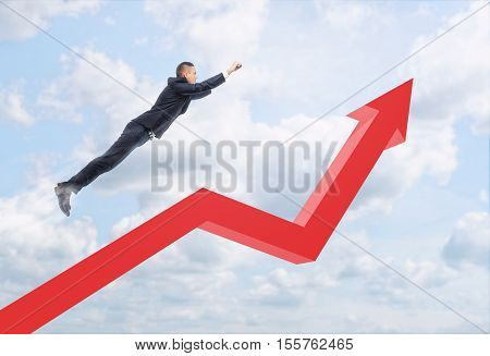 Businessman in a pose of Superhero flying over the red arrow on a background of the sky. Rapid success. Professional and career development. Business and management. Way to success. Reaching aims.