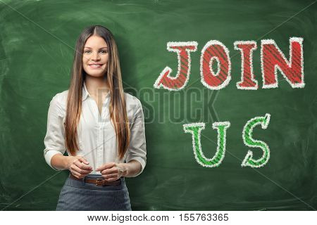 A young beautiful woman standing near the big bright words 'join us' written on the green chalkboard. Looking for the new members. We need you. The company is recruiting. An increase in the number of the staff .