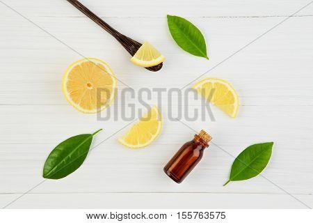 Fresh Lemons And Lemons Leaves With Essential Oil On Rustic Wooden Background. Fresh Lemons And Lemo