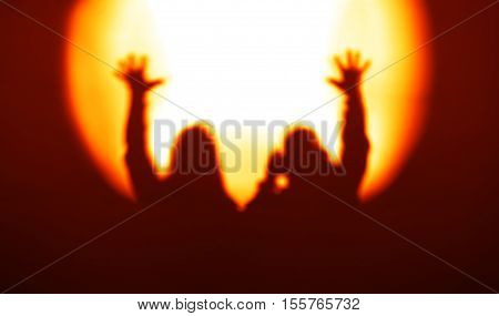 Orange couple silhouettes with hands up in light of floodlight backdrop hd