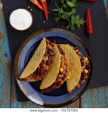 Three tacos with chili con carne in a bowl next to the fresh chili peppers and parsley
