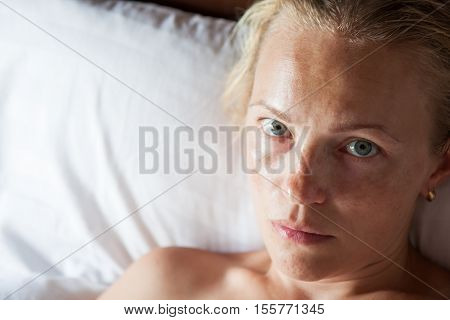 Dissatisfied lonely woman portrait on bed with copy space