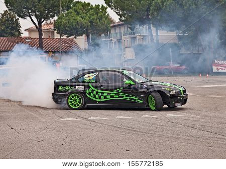 SAN PIETRO IN VINCOLI, RAVENNA, ITALY - OCTOBER 23: driver and co-driver on a drift racing car BMW in action drifting with smoking tires  in