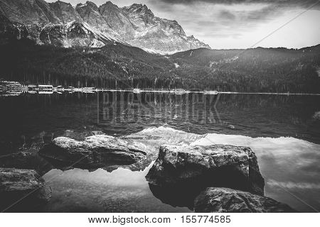 Dramatic scenery with the German Alps mountains reflected in the Eibsee lake. Image depicting tranquility and meditation.