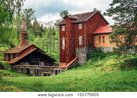Old ironworks, red wooden building. standing in a lush green environment.