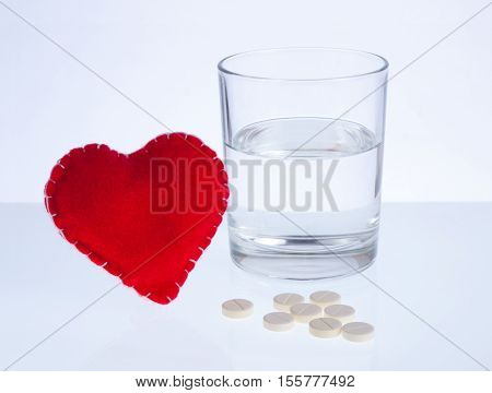 Red heart glass of water and pills